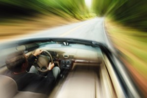 lifestyle photograph of a caucasian man driving fast down a road in a convertible